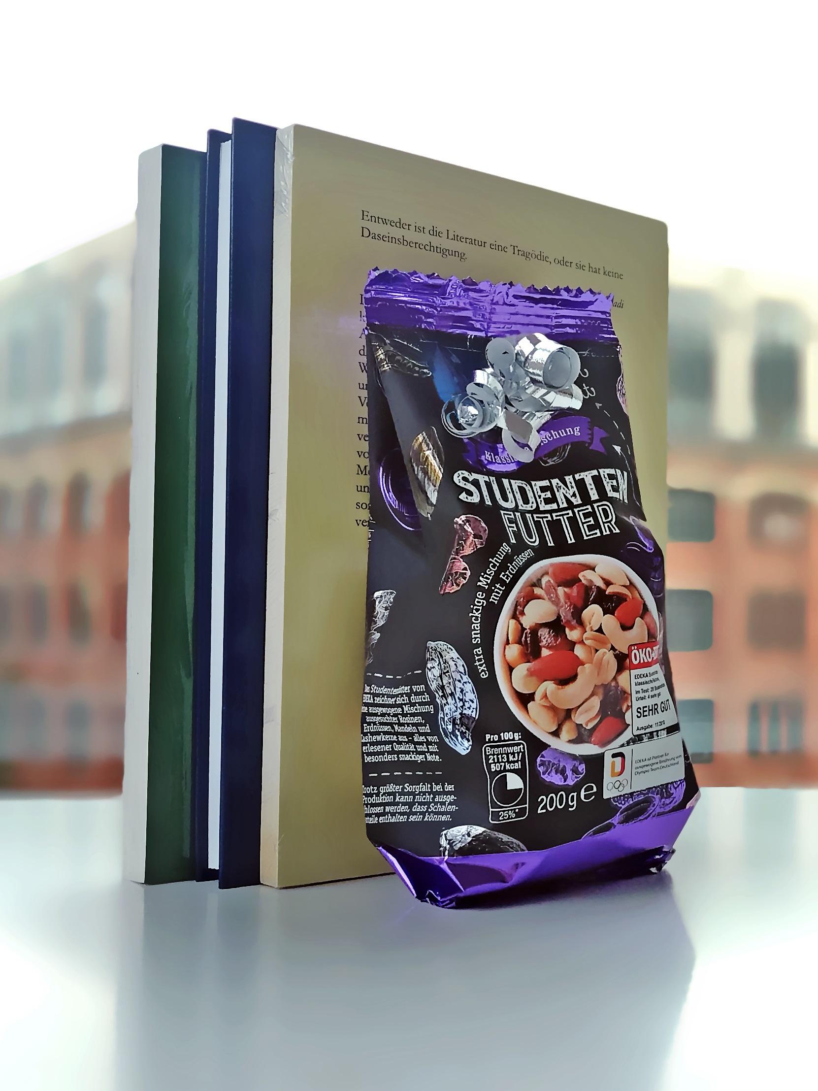 Zus sehen ist das Angebot Studierendenfutter - Buchpaket für Arabistik mit Studentenfutter und drei Büchern vor einer Glaswand